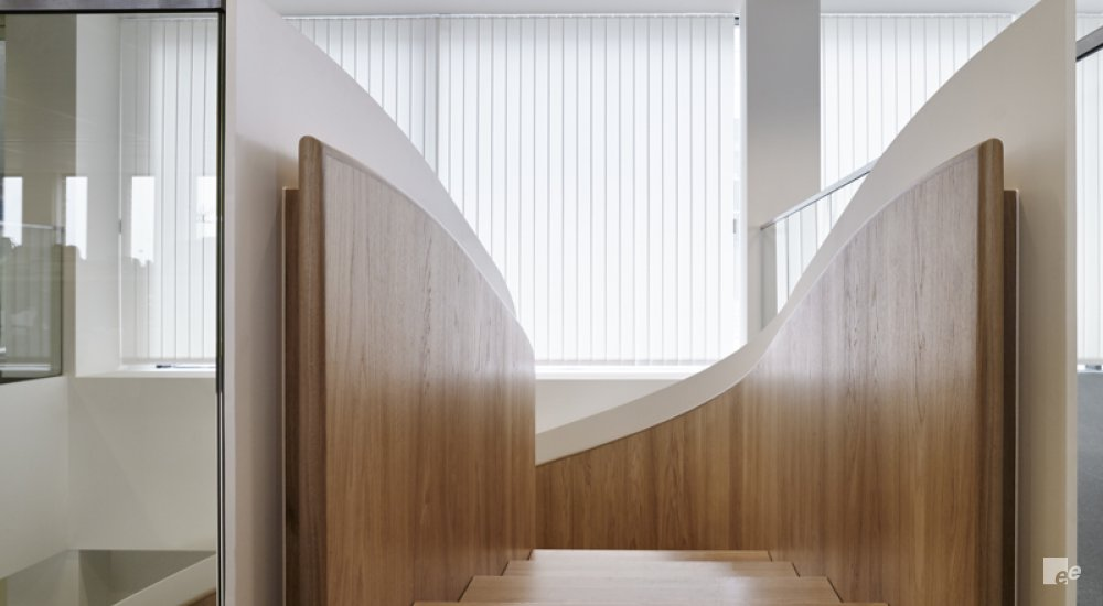 The top of the spiral staircase in the Mediahuis with wooden floors, fluorescent lights from the modular ceiling and blinds in front of the windows