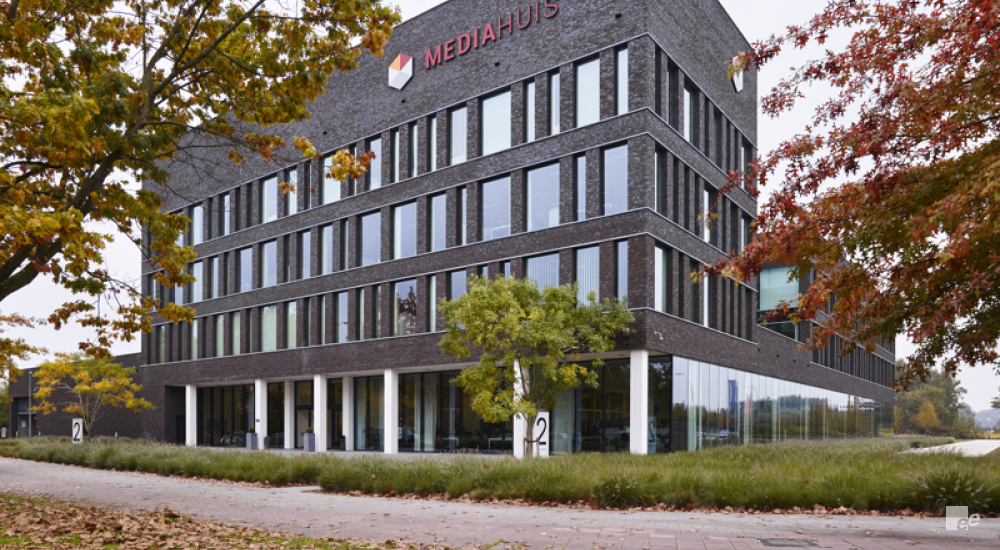 The exterior of the office building of the Mediahuis in Antwerp, outside are trees, shrubs, grass and the road.