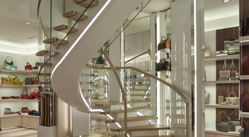 A spiral staircase with clear glass railings and natural oak steps. Bags are stalled up in the shop.