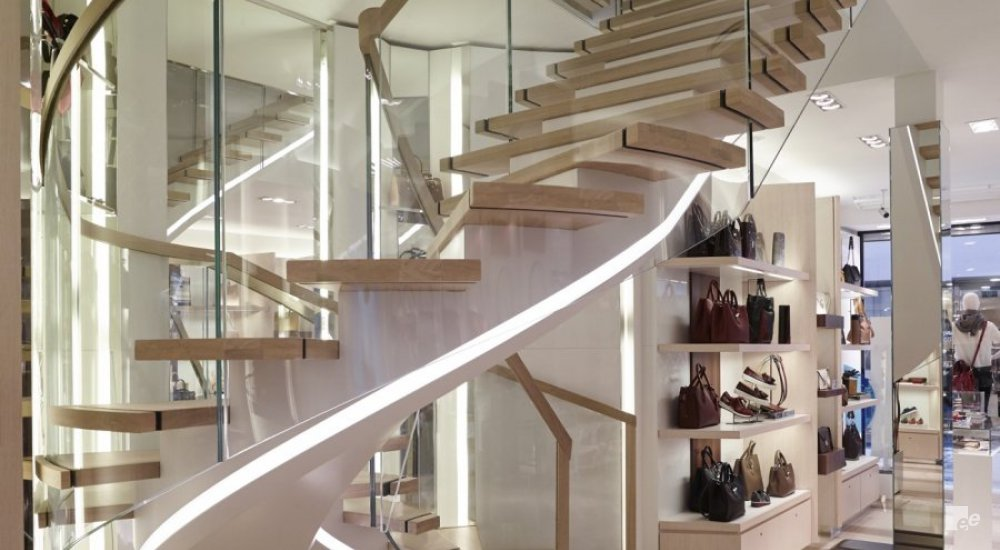 A spiral staircase with clear glass railings and natural oak steps.