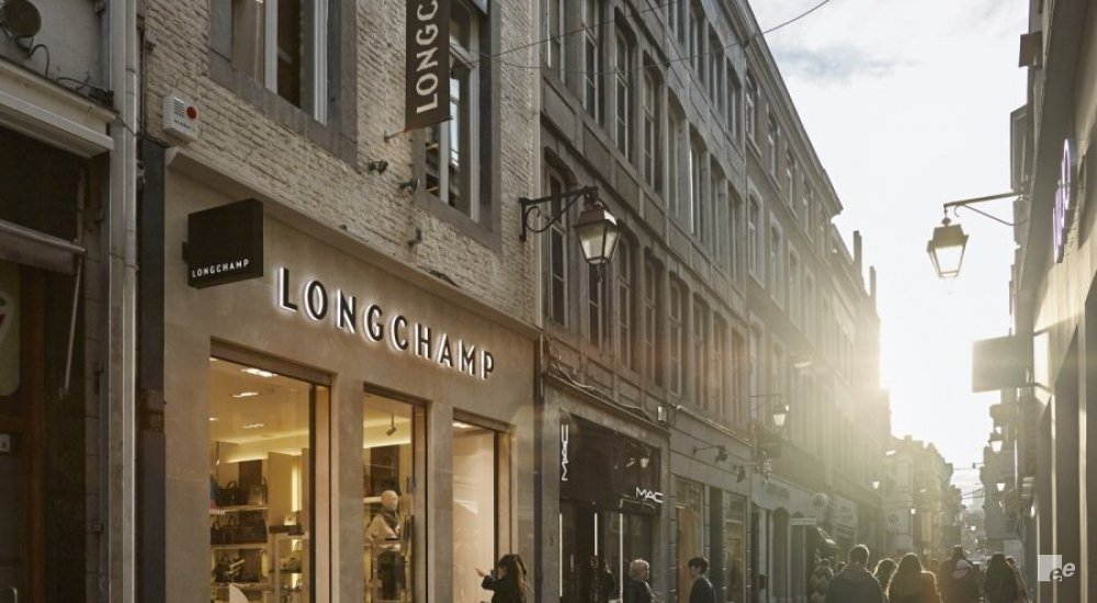 The exterior of Longchamp Paris, in a shopping street with people.