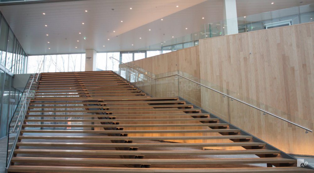 A wide staircase with wooden finish. The oak wooden steps are reinforced with steel. Glass railing.