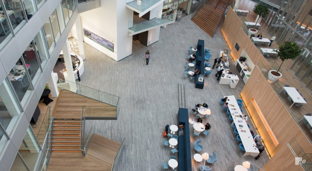 Overview of the hall at The Edge in Amsterdam, with two wooden staircases, tables and armchairs.
