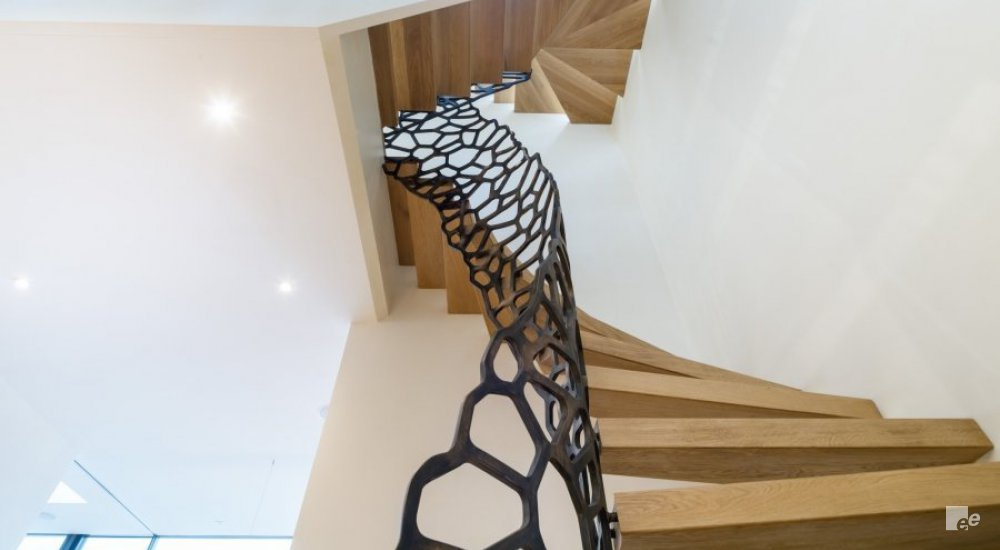 Bottom view of a staircase with oak wooden steps and antique bronze metallic balustrade with cell design.
