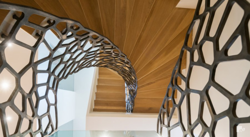 Top view of a floating staircase with wooden steps, and balustrades with a metallic cell design.